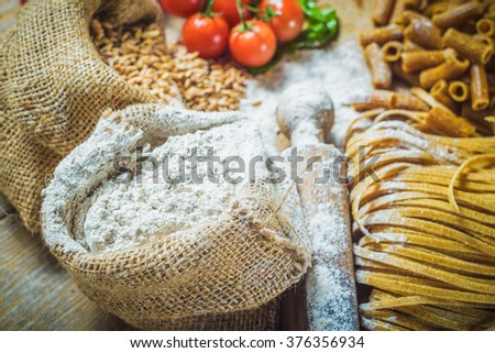 Integral components of tagliatelle pasta ingredients and tomatoes. - stock photo