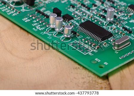 Integrated circuit (IC) and other microelectronic components such as capacitors, resistor and crystal on green PCB with wooden desk background. - stock photo