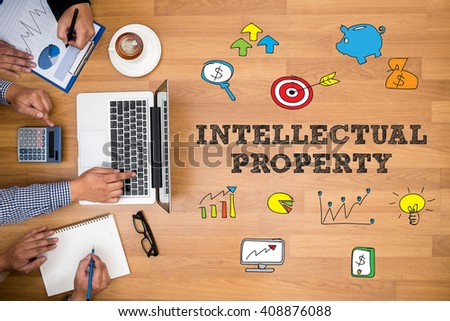 INTELLECTUAL PROPERTY Business team hands at work with financial reports and a laptop - stock photo