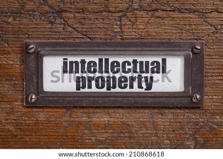 intellectual property  - file cabinet label, bronze holder against grunge and scratched wood - stock photo