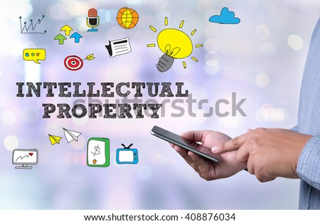 INTELLECTUAL PROPERTY person holding a smartphone on blurred cityscape background - stock photo