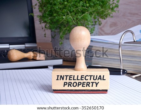 Intellectual Property Stamp with binder and laptop in the Office - stock photo