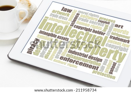 intellectual property word cloud on a digital tablet with a cup of coffee - stock photo