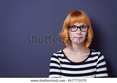 Intellectual young woman in dark framed glasses standing staring intently at the camera in a trendy striped top over blue with copy space