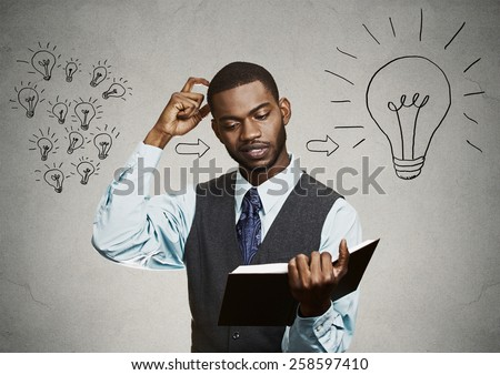 Intelligence knowledge. Closeup portrait smart handsome man student holding a book scratching head has big ideas isolated on gray wall background. Face expression attitude life perception dynamism  - stock photo