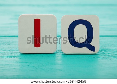 Intelligence quotient. Word IQ on blue wooden background - stock photo