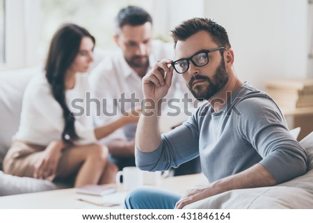 Intelligent and confident. Confident mature man holding looking over shoulder and adjusting his glasses while another man and woman sitting in the background   - stock photo