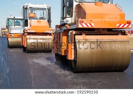 Intelligent Compaction for Asphalt Concrete Surface by Vibratory Rollers Machines during Road Construction Works - stock photo