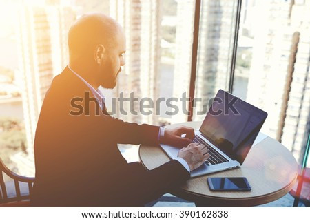 Intelligent man managing director is keyboarding on laptop computer, while is sitting in modern office interior. Successful male economist is analyzing the activities of the company via net-book - stock photo