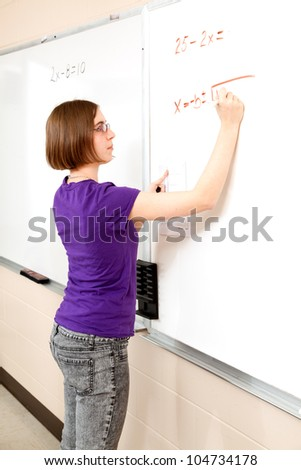 Intelligent teen girl working advanced mathematics problem on the board. - stock photo
