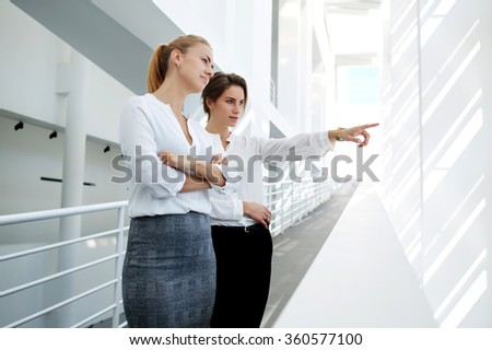 Intelligent woman lawyer showing to partner their clients which visible through window while standing in office hallway, professional employee points to something while her colleague looking on this - stock photo