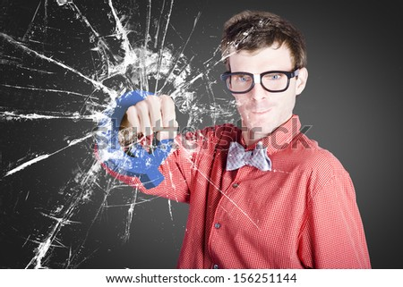 Intelligent young man working on an idea while punching through glass wall with question mark Q. Solution or breakthrough concept - stock photo