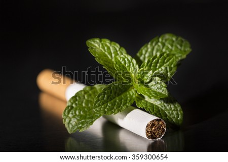Intenational day : do not smoke today, May 31 - 2016.  End of flavored plug wrap cigarette cigarette with fresh mint, on black background - stock photo