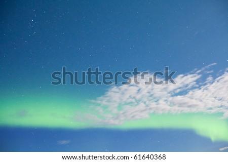 Intense Aurora borealis (northern lights) showing between clouds during moon lit night. - stock photo