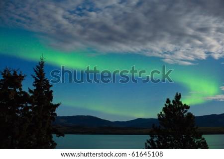 Intense Aurora borealis showing between clouds during moon lit night over Lake Laberge, Yukon Territory, Canada. - stock photo