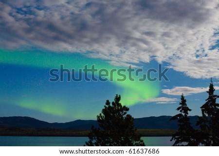 Intense Aurora borealis showing between clouds during moon lit night over Lake Laberge, Yukon T., Canada. - stock photo