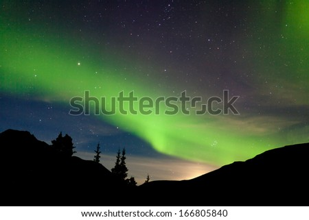 Intense bands of Northern lights or Aurora borealis or Polar lights dancing on night sky over hills with light glowing from moon rising behind them,Yukon Territory, Canada - stock photo