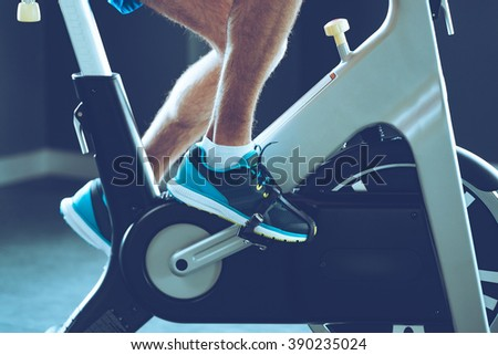 Intense cardio workout. Side view close-up part of young man in sports shoes cycling at gym - stock photo