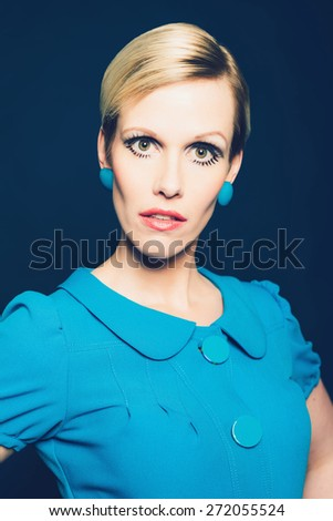 Intense fashionable young woman with short blond hair in a blue dress and matching earrings staring directly at the camera - stock photo