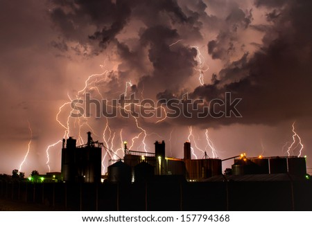 Intense lightning storm behind a grain elevator. - stock photo