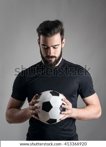 Intense portrait of football player holding and looking at the ball focused over gray studio background. Determination concept.  - stock photo
