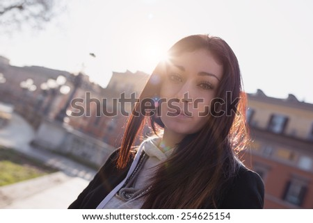 Intense portrait of young woman in the city. Filtered image with back light effect.