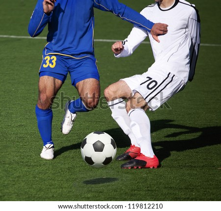 intense struggle for the ball on the soccer field - stock photo