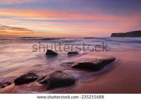 Intense summer sunrise colours at Bungan Beach and mesmerising ocean flows.   Permanent visible rips to each side and shifting rips in the centre a hazardous beach rated 7/10 (highly hazardous) - stock photo