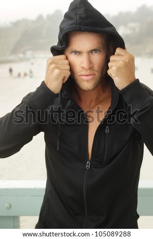 Intense young man in black hooded workout clothing outdoors - stock photo
