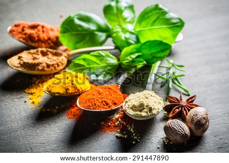 Intensive spices and herbs on old table - stock photo