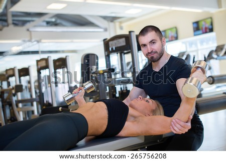 Intensive training together. Couple of young and beautiful people is having workout in a gym. Perfect shape. Sportsmen. Hard workout in a gym. Athlete people