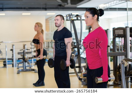 Intensive training together. Portrait of young and pretty athlete girl in a gym. Other people are training on the background. Perfect shape and proper training.
