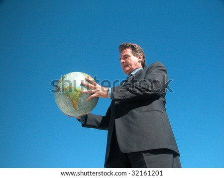 Intent Business man holding globe with both hands - stock photo