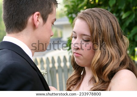 Intent Prom Girl Fixing Boutonniere - stock photo