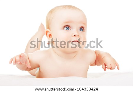 interested child lays on white fabric