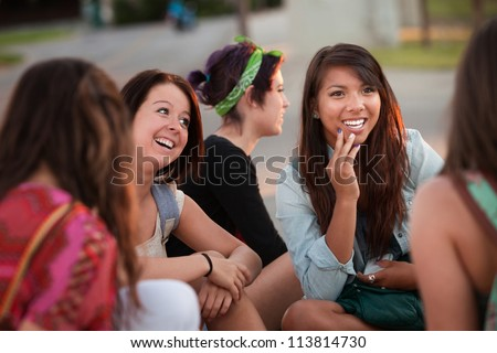 Interested female teenager in conversation with friends - stock photo