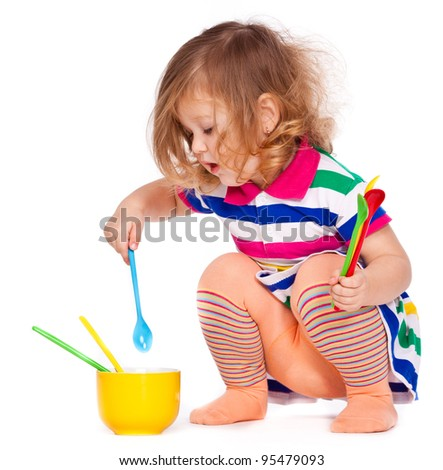 Interested little girl plays with dishes