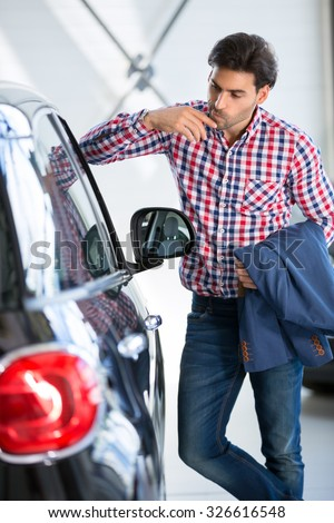 Interested man  examines a new car in showroom, leaning against it watch at the interior of a new car - stock photo