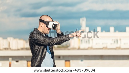 Interested young wearing a pair of VR glasses and pointing with his finger to the blue sky background on the rooftop building excited by augmented reality cityscape