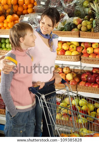 Interesting boy with mom chooses products in the store