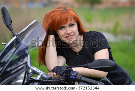 Interesting,cheerful,smiling,pretty,nice,good,friendly,lovely,adorable,redhead,red-haired professional biker girl with black,fast motorcycle,motorbike,bike,cute smile.Girl with motorbike,fast rider. - stock photo