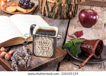 interesting cup of tea with message on a wooden table with a strainer on a plate next to cup and open old book, autumn decoration - stock photo