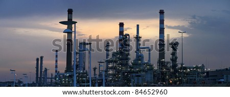 Interesting panorama of an oil refinery near a road  in the early morning light (dawn) - stock photo