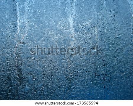 Interesting pattern of frozen water of glass window - stock photo