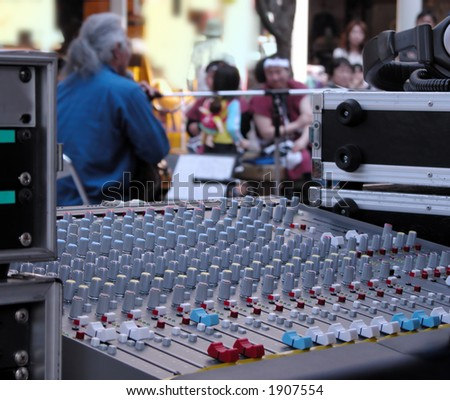 Interesting perspective of a street music performance. Selective focus on the sound master command desk, the artist and the audience are out of focus.
