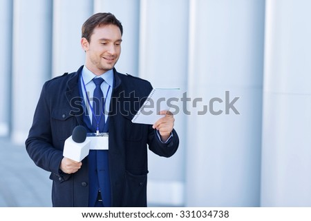 Interesting thoughts. Young smiling newsman is engrossed with something written in the notebook.  - stock photo