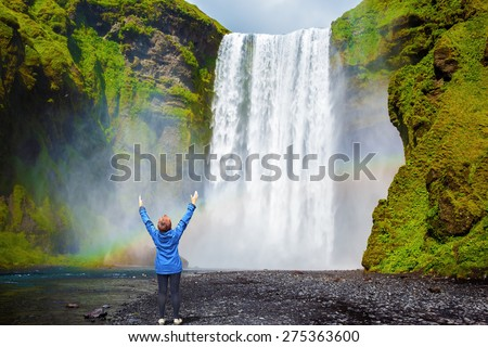 Interesting waterfall in Iceland - Skogafoss. Picturesque huge rainbow appears in the water mist. Middle-aged woman - tourist shocked beauty waterfall - stock photo