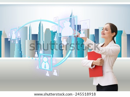 Interface business office of the future, a woman in office with skyscrapers on background pushing on virtual buttons - stock photo