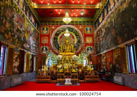 "Interior architecture photo of a grand hall of temple ""Wat Sameannari"" with golden lord Buddha statue and mural paintings wall about Buddha story in Bangkok, Thailand. It is  public domain for tourism"