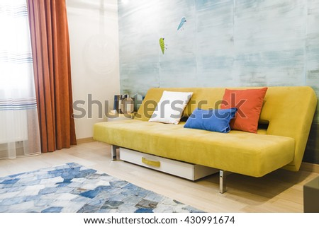 interior background. yellow or brown Sofa with colorful pillows in children room stand against blue wall with birds. orange and transparent curtains. - stock photo